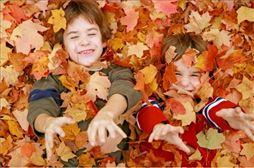 niños tirados en el suelo con hojas otoñales