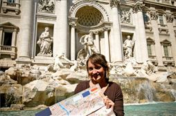 Chica en su viaje de estudios frente de monumento Romano